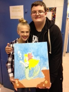 2 students posing with a painting of a mermaid